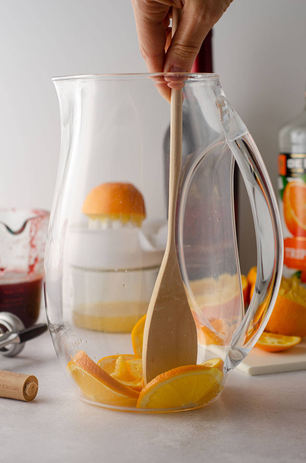 muddling oranges in a pitcher with a wooden spoon