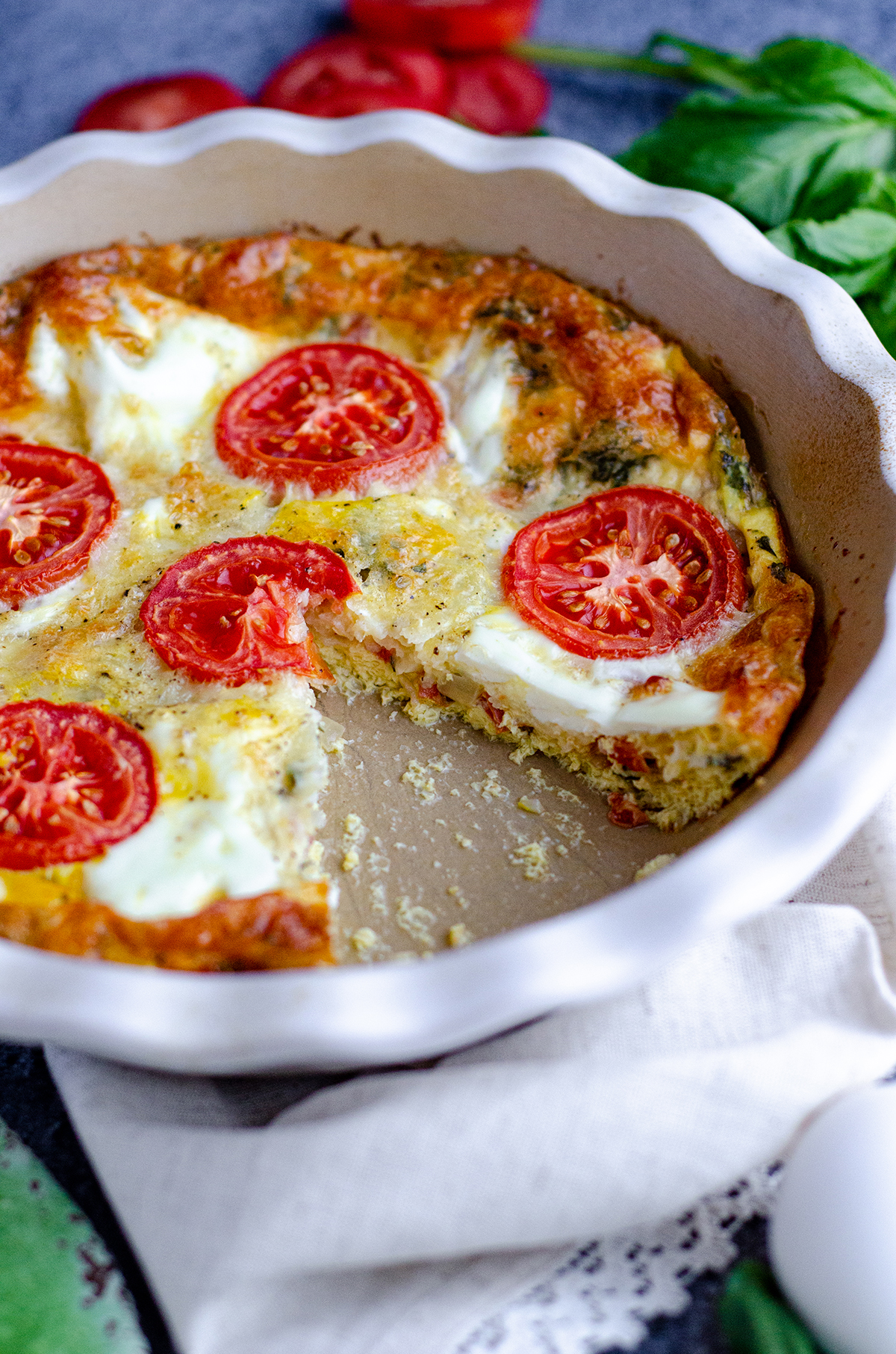 crustless caprese quiche in a pie plate with a slice removed