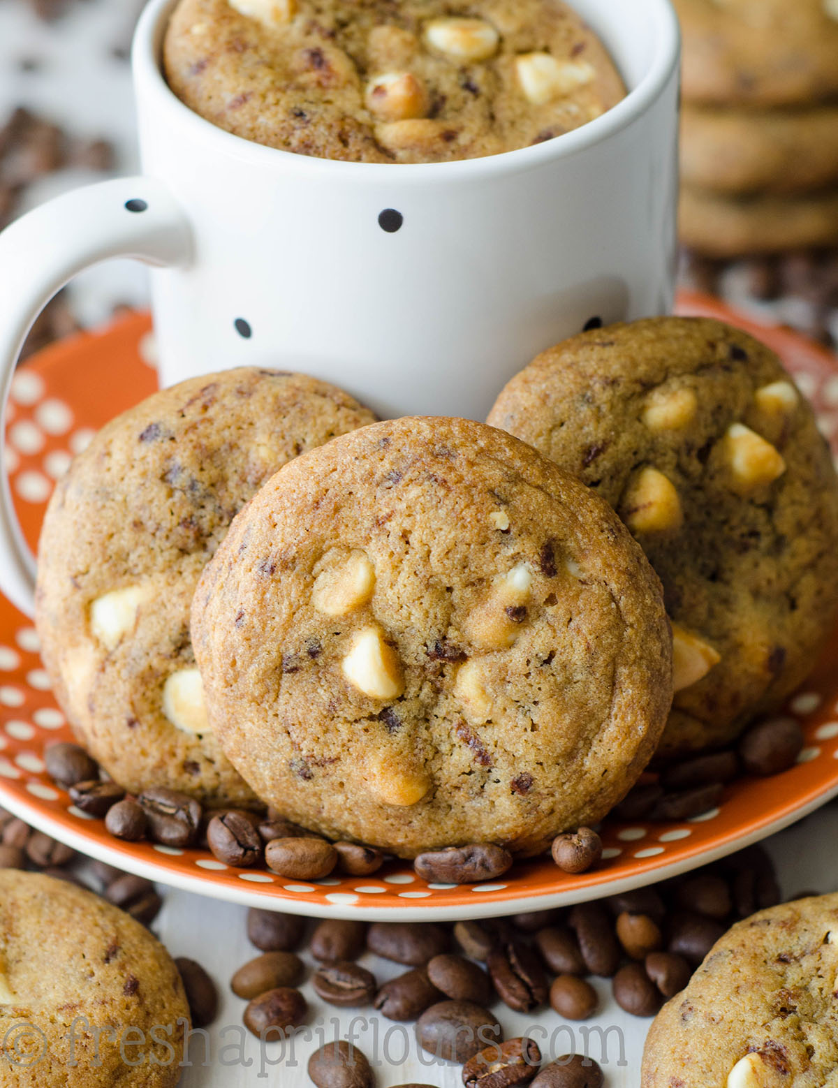 cappuccino cookies on a plate with coffee beans and a mug of coffee