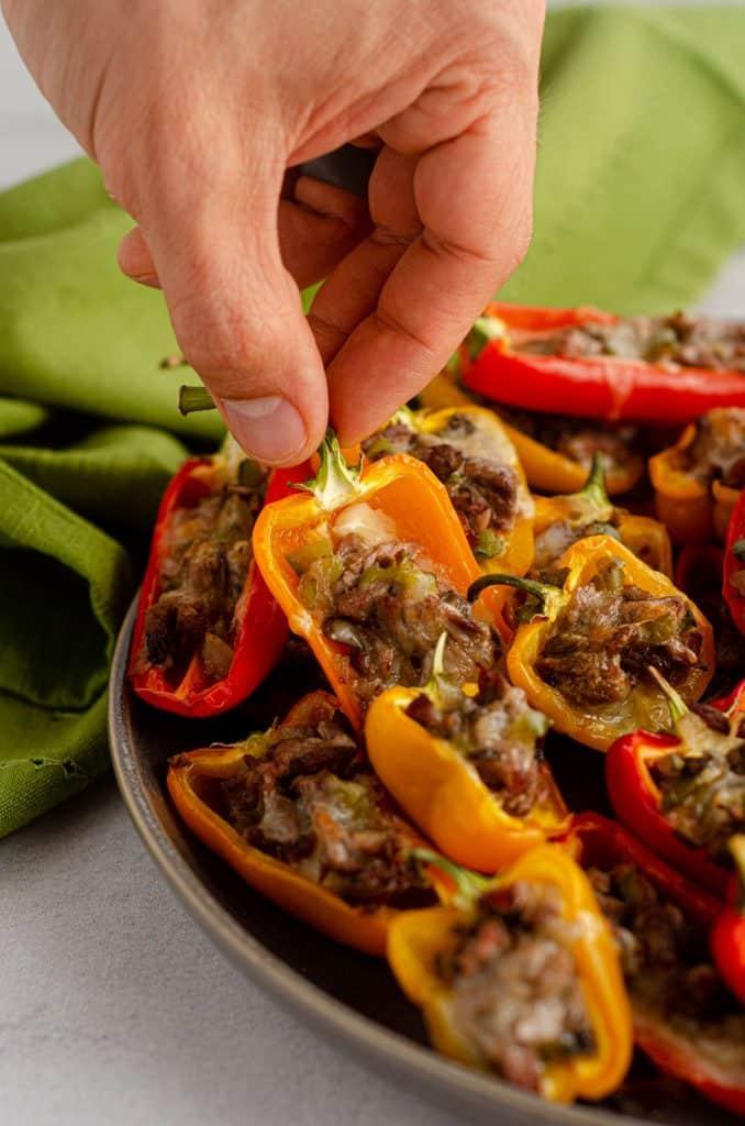 hand grabbing mini philly cheesesteak stuffed pepper off of a platter