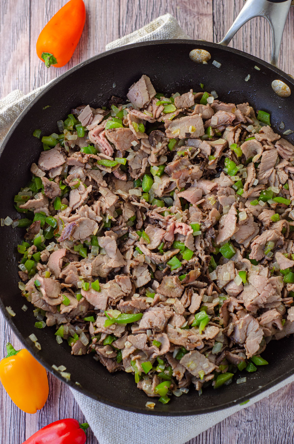 meat, peppers, mushrooms, and onions in a frying pan