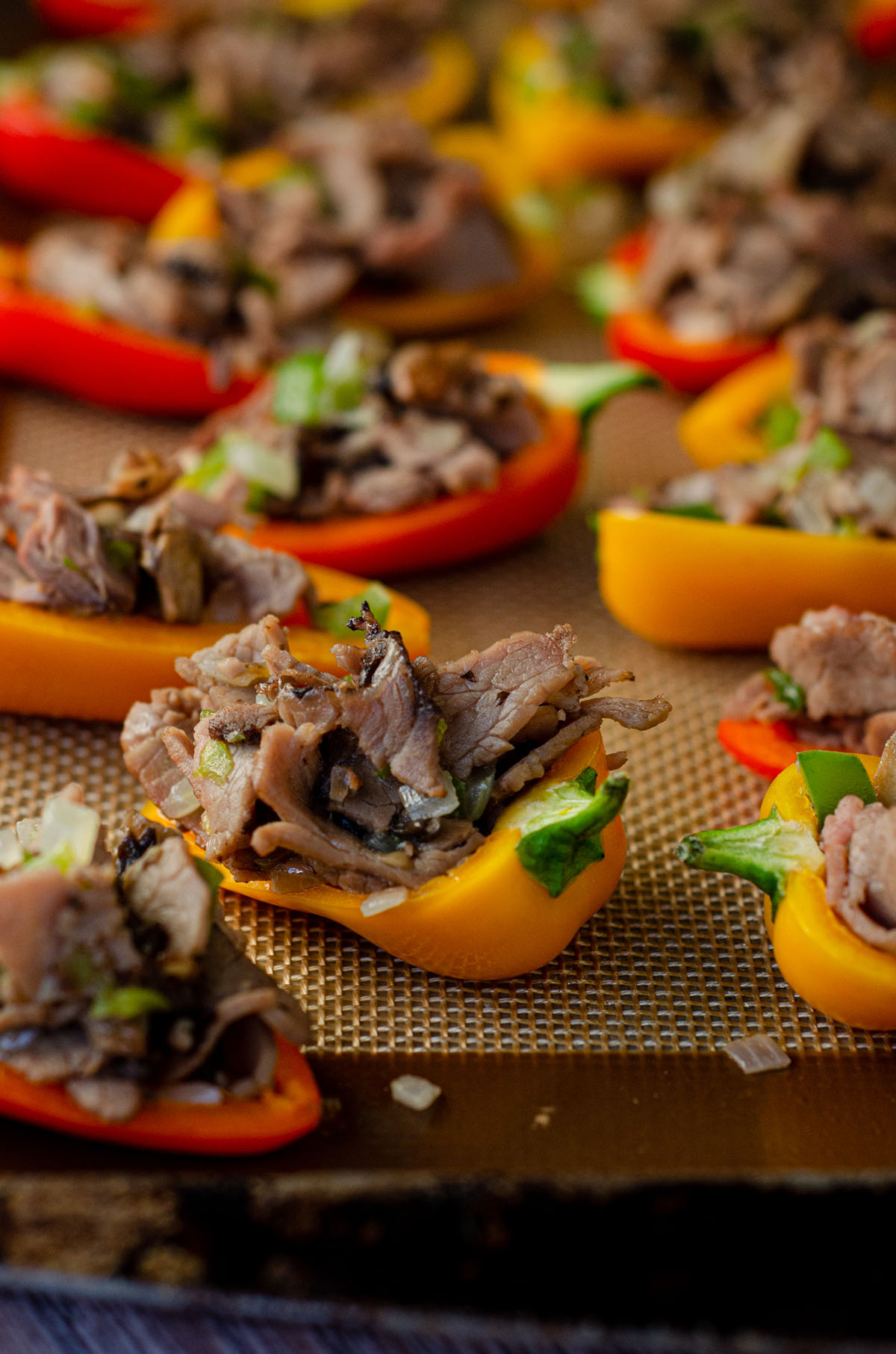 mini bell peppers on a baking sheet stuffed with filling and ready to bake