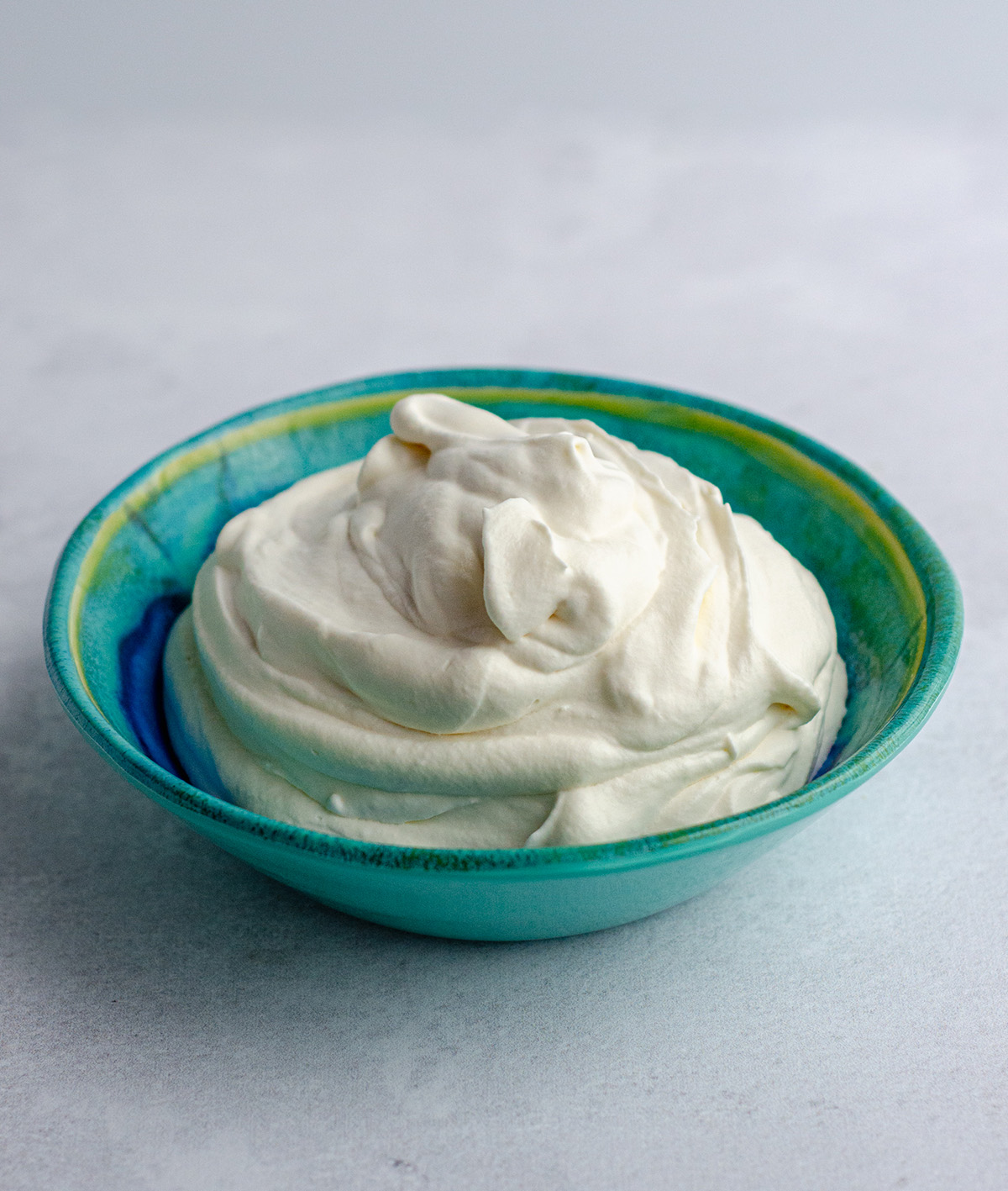 homemade whipped cream in a blue and green bowl