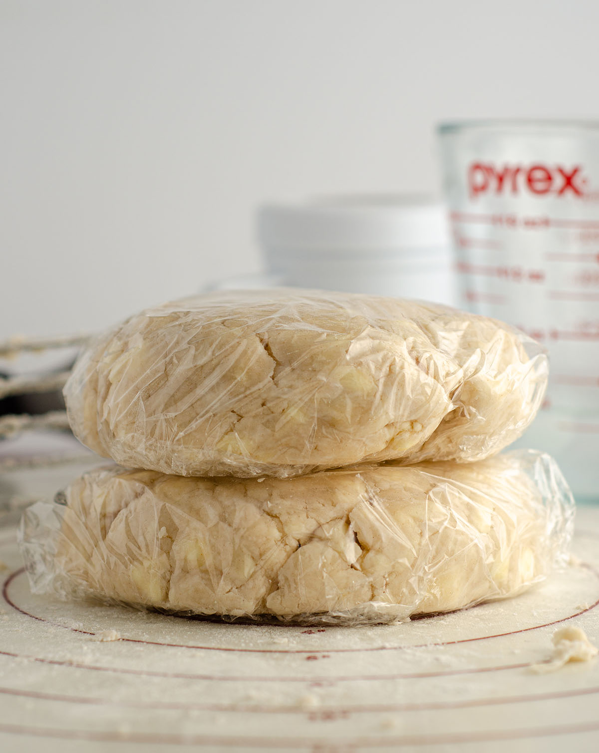two discs of pie dough wrapped in plastic wrap ready to chill