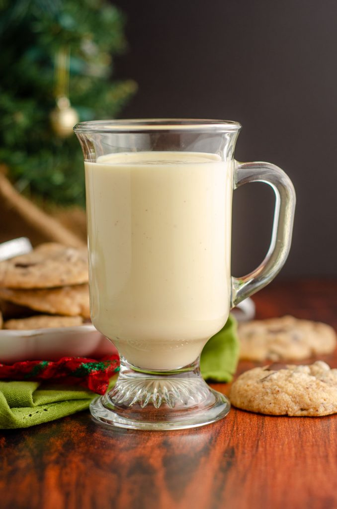 glass of eggnog with eggnog chocolate chunk cookies behind it