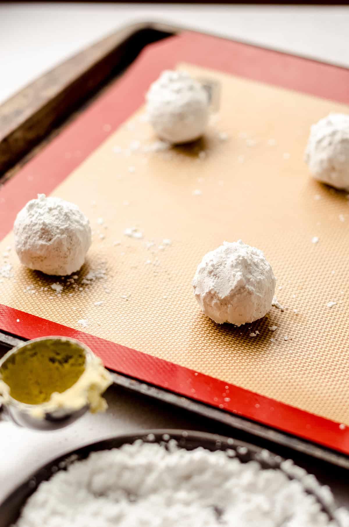 lemon crinkle cookie dough balls coated in powdered sugar on a baking sheet