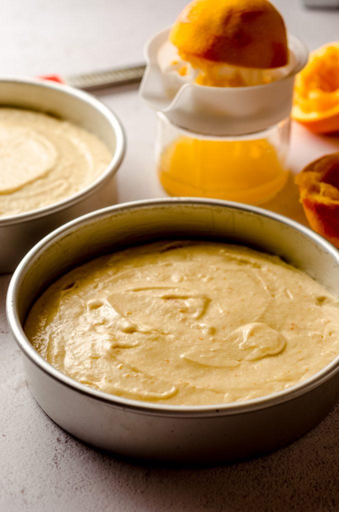 orange creamsicle layer cake batter in a baking pan