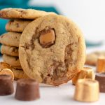 peanut butter rolo cookie sitting in front of a stack of cookies with scattered rolos