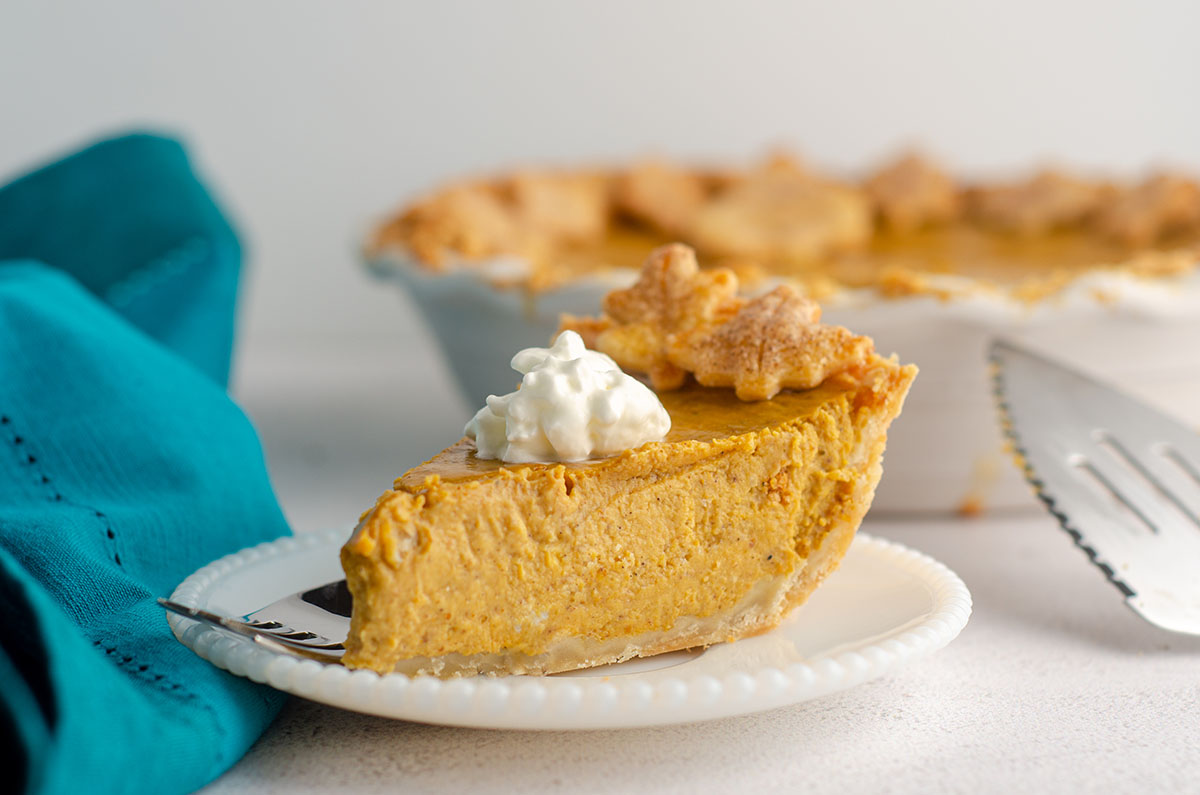 side view of slice of pumpkin pie with a dollop of whipped cream on a plate with a fork
