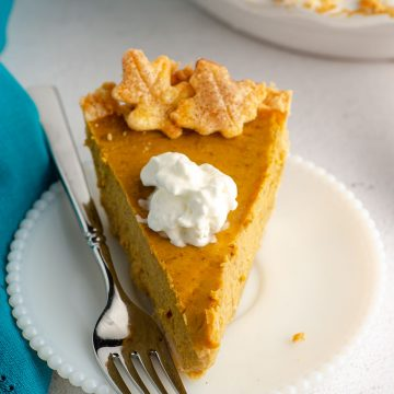slice of pumpkin pie with a dollop of whipped cream on a plate with a fork