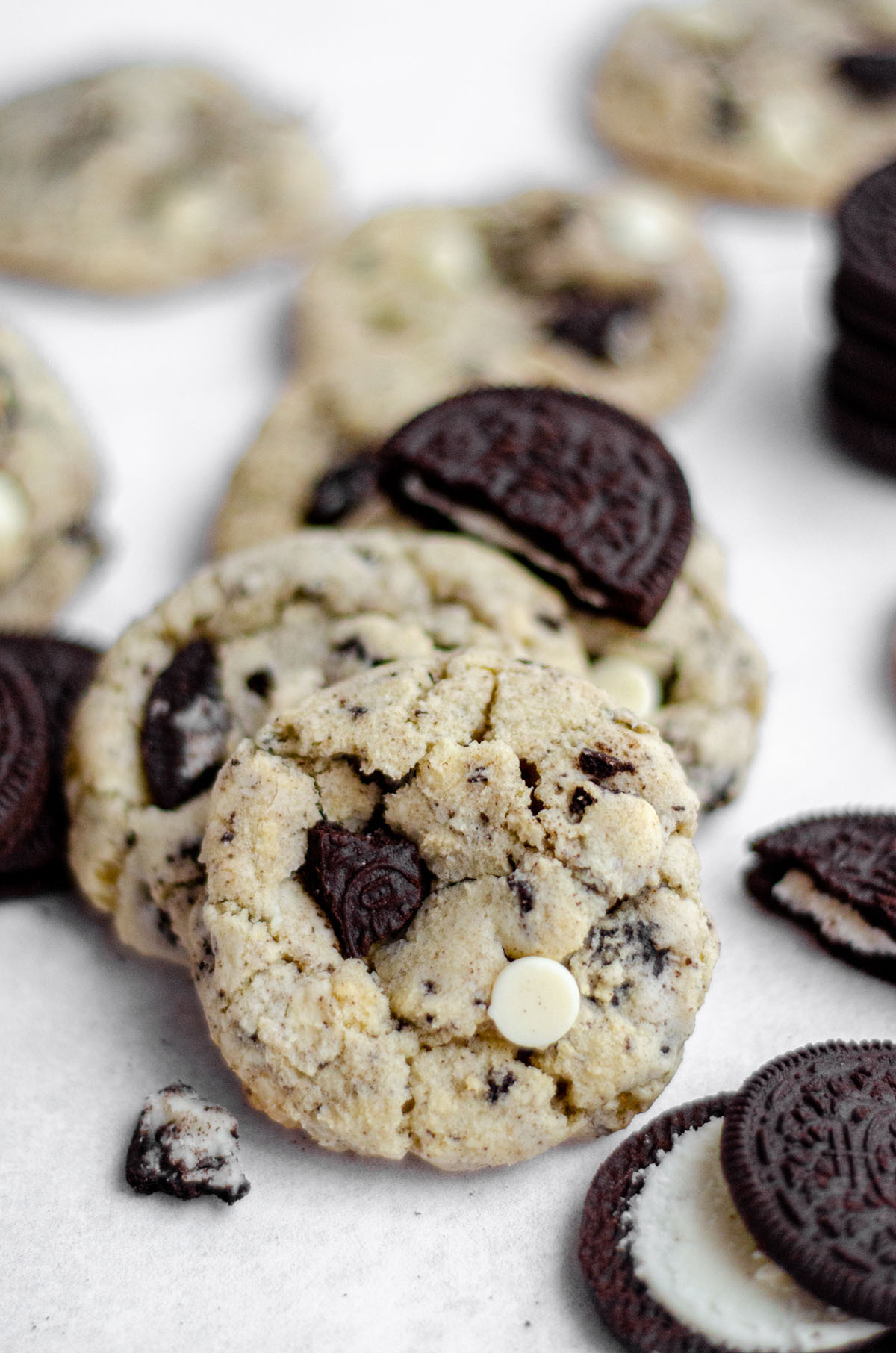 cookies and cream cookies on a white surface with oreo cookies scattered around it