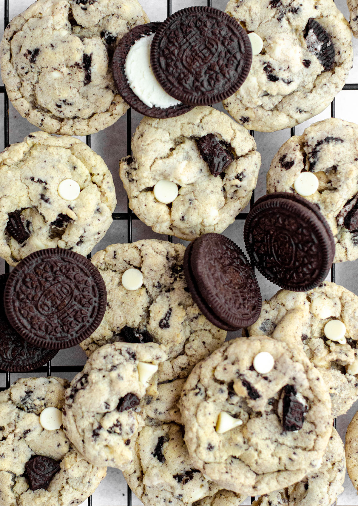 aerial photo of cookies and cream cookies on a cooling rack with oreos scattered around them