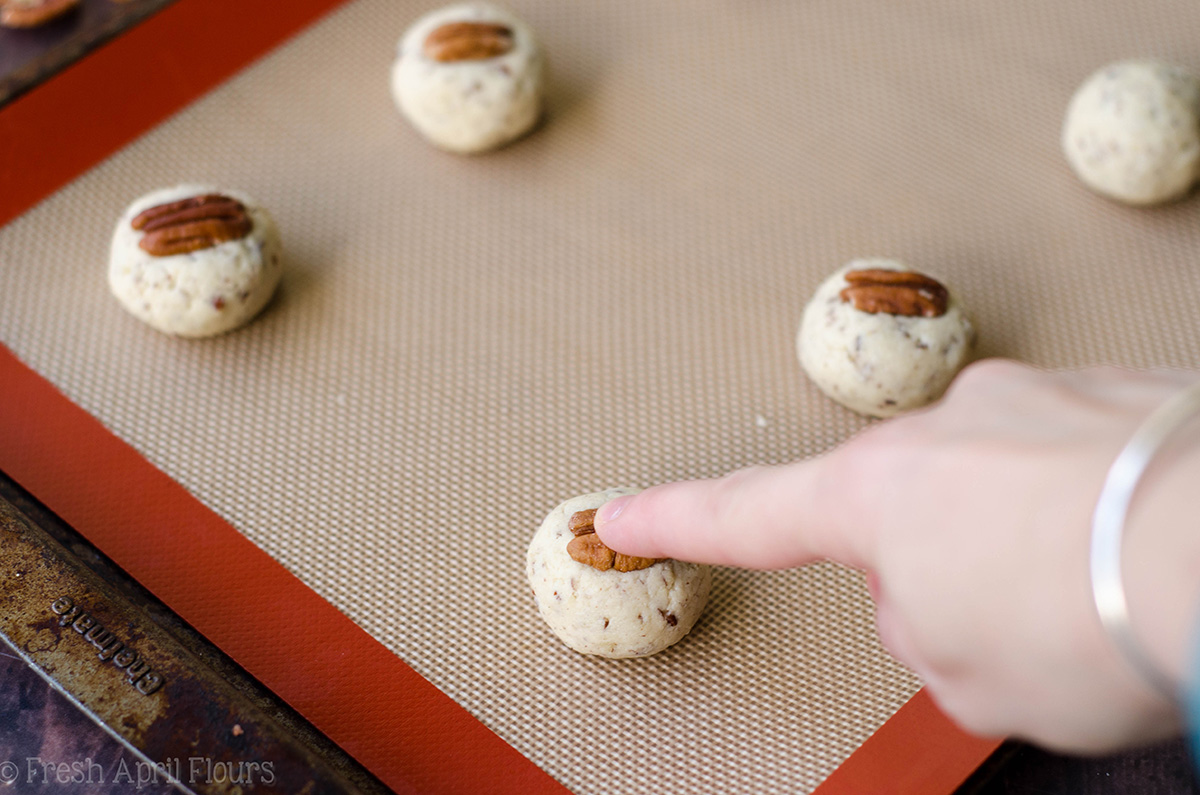 pressing pecans into cookie dough balls