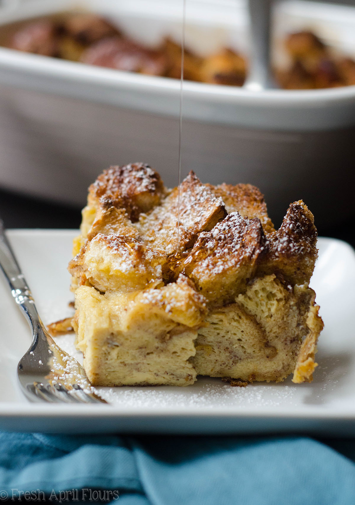 french toast casserole on a plate with syrup dripping onto it