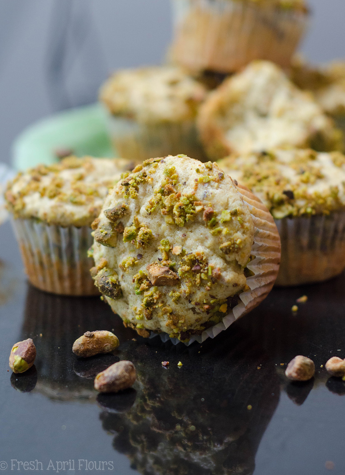 pistachio muffin on its side with muffins behind it