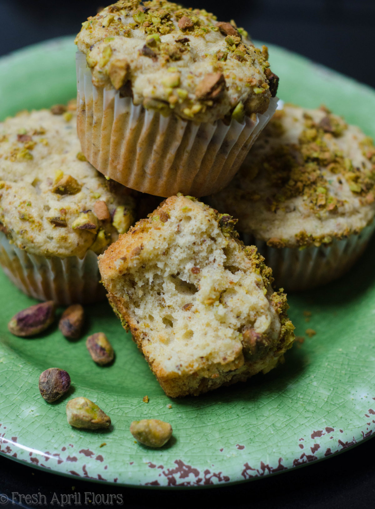 pistachio muffins on a plate and one has a bite taken out of it