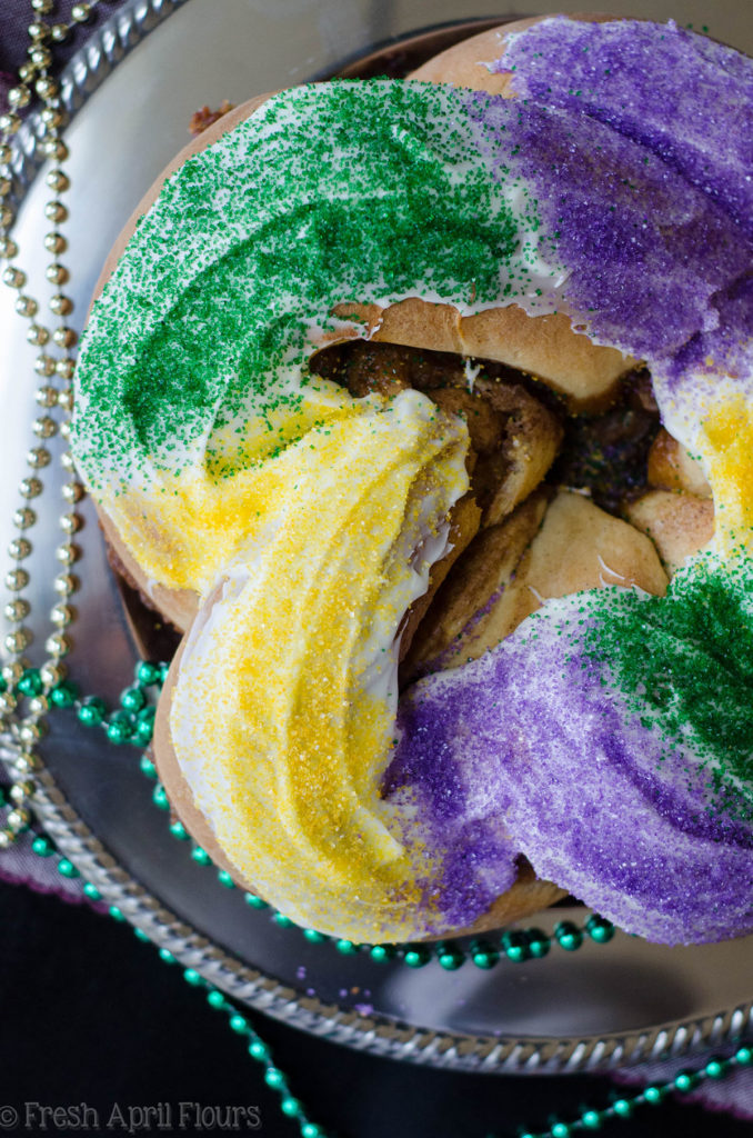 Mardi Gras King Cake: A simple spiced yeast dough is filled with a cinnamon sugar filling, twisted into a ring, and adorned with colored sugar.