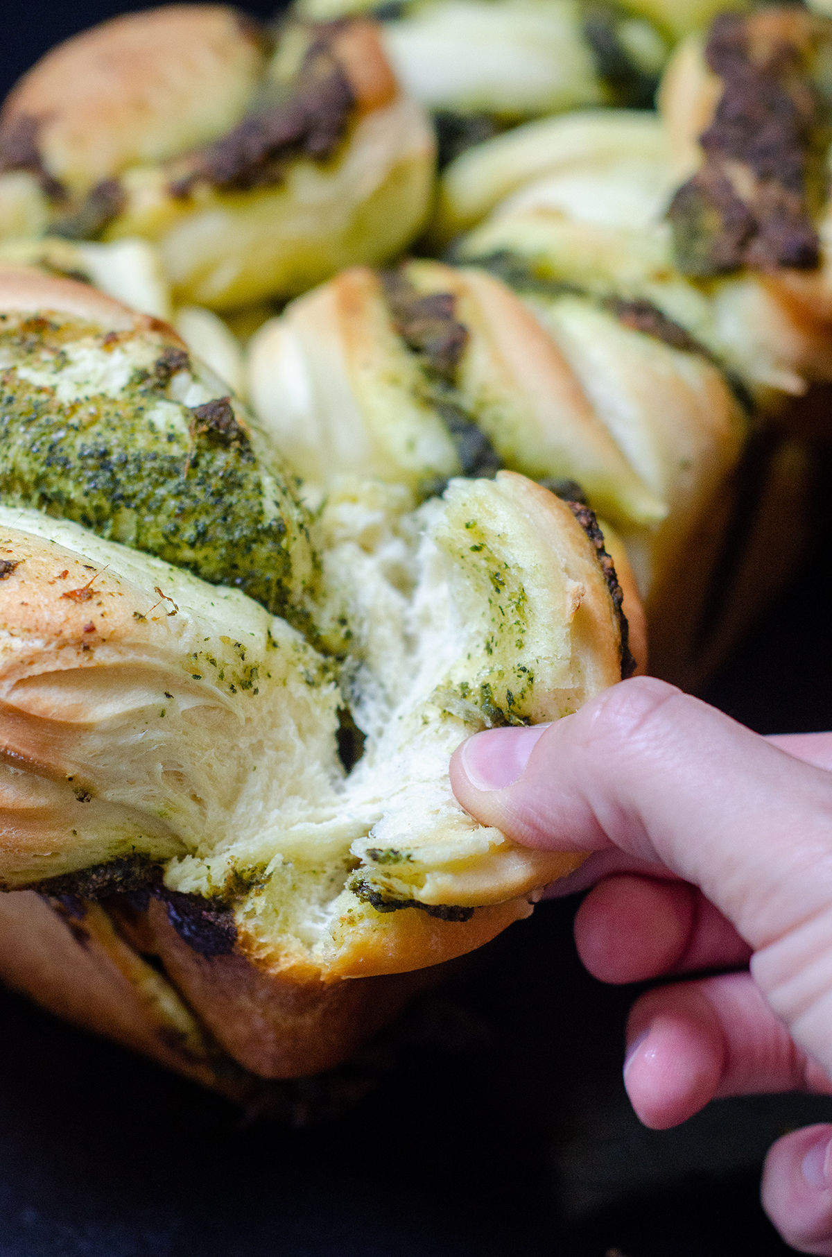 pesto pull-apart bread being pulled apart by a hand
