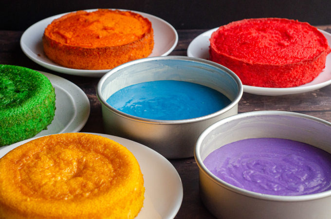 Learn how to make a beautifully colorful rainbow cake, as tall or as short as you want it to be. Find instructions for scaling cake to your needs and how to efficiently create 6 layers of cake, even if you only have 2 pans.