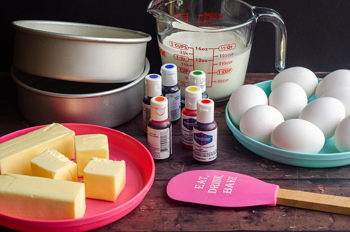 mise en place for a rainbow cake: a plate of butter, cake pans, gel coloring, a spatula, a measuring cup of milk, and a plate full of eggs