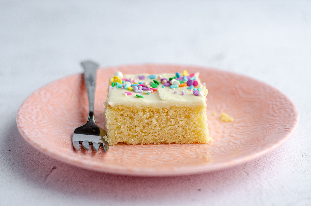slice of white sheet cake on a pink plate with a fork