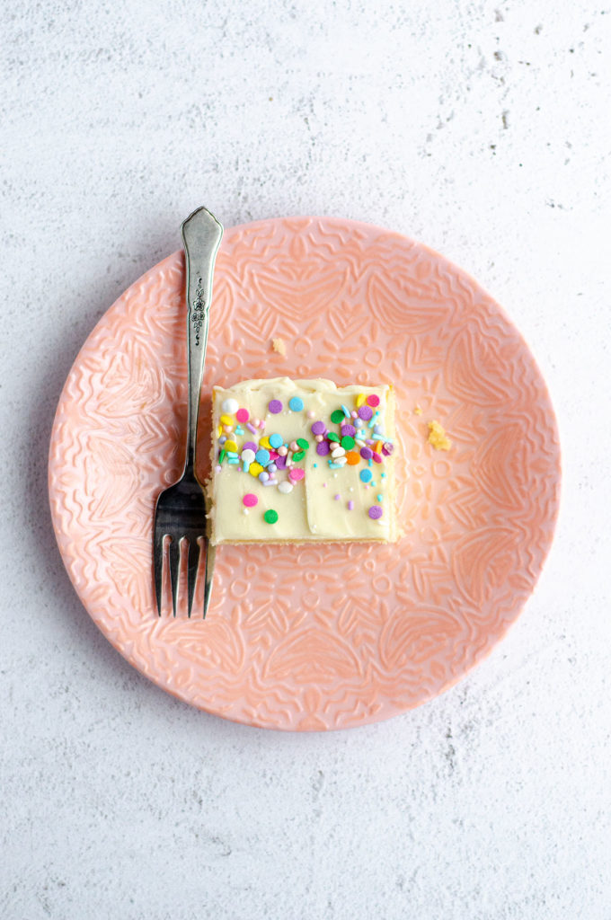 aerial shot of white sheet cake slice on a pink plate with a fork