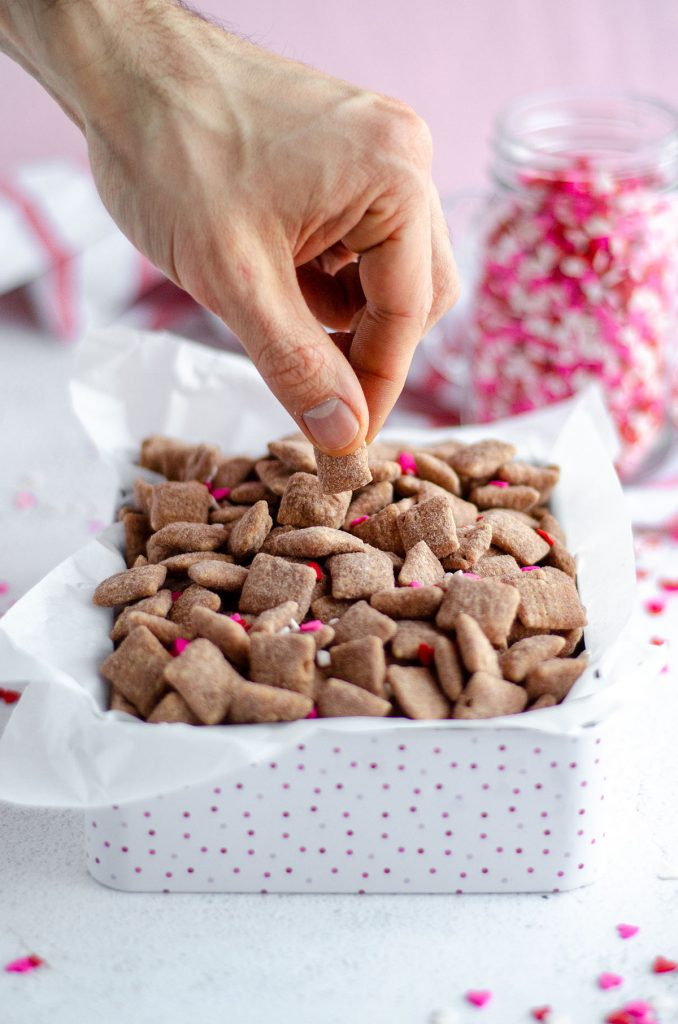 hand grabbing some red velvet puppy chow out of a treat box