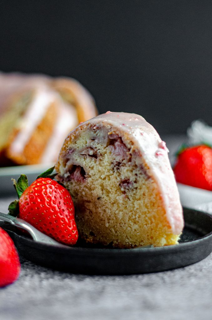 slice of a strawberry bundt cake on a plate with a strawberry as garnish