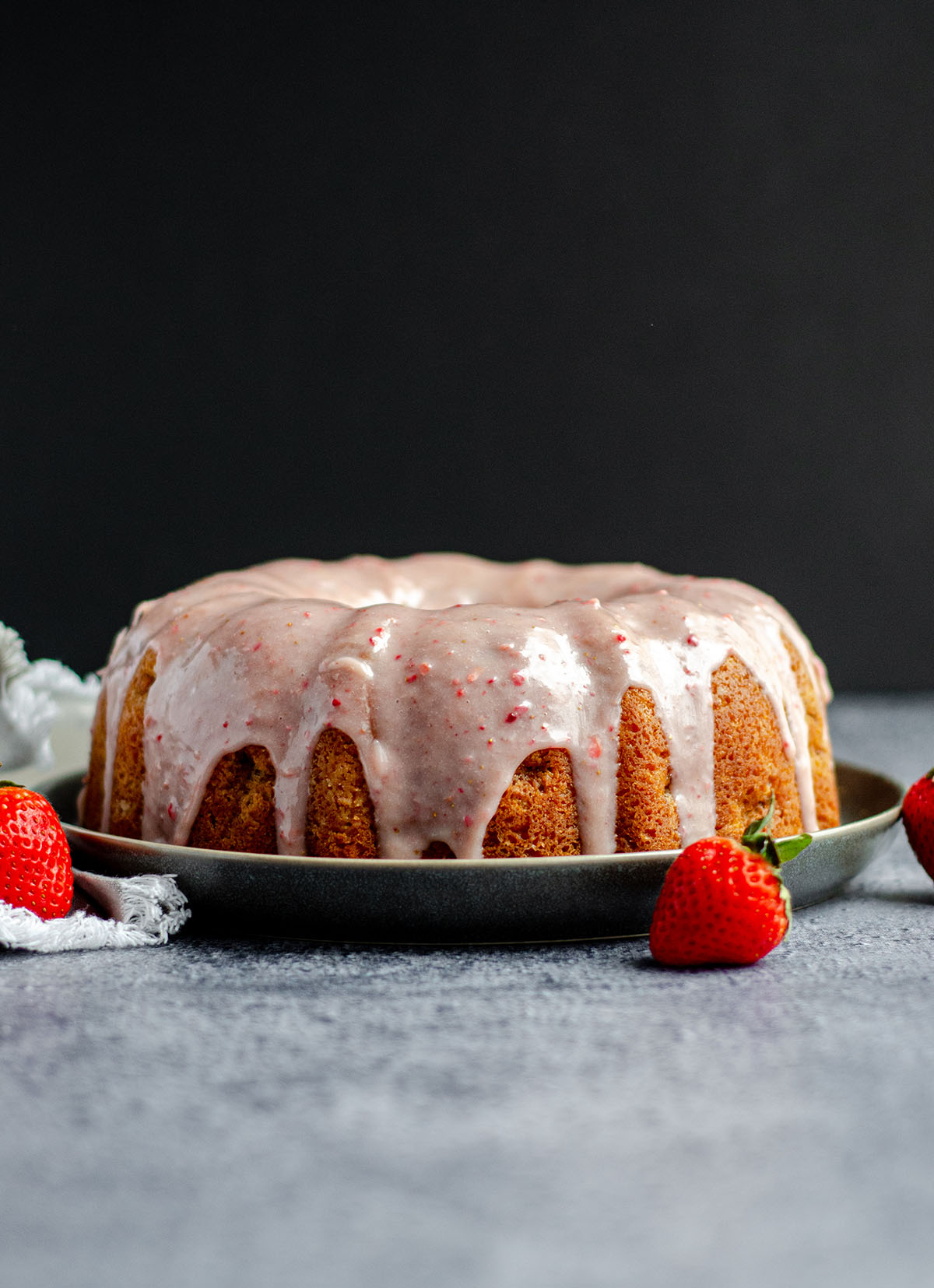 Homemade strawberry bundt cake made from scratch with fresh strawberries and topped with strawberry white chocolate ganache.