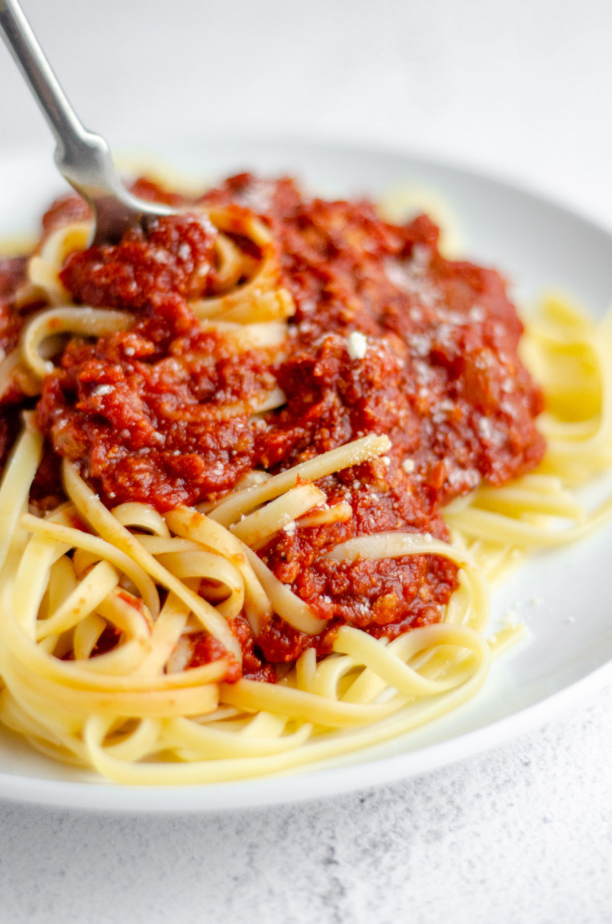 plate of spaghetti with meat sauce with a fork twirling some pasta