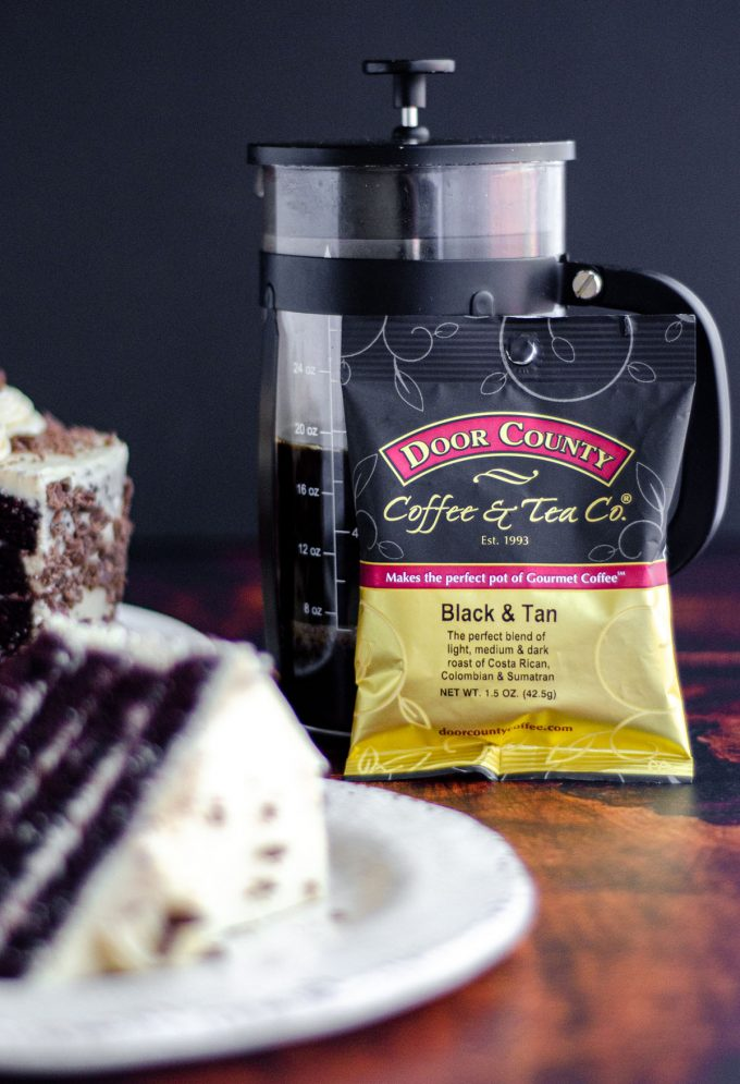 bag of door county coffee leaning up against a french press with a slice of mocha cake in the foreground