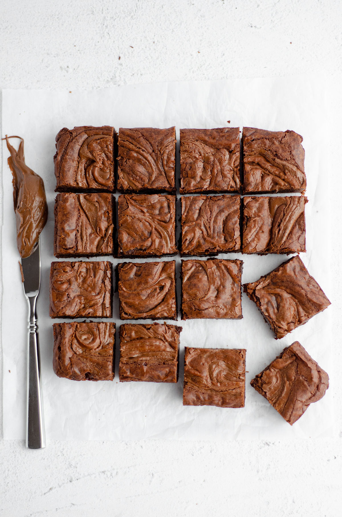 aerial photo of sliced fudgy nutella brownies with a knife with nutella on it next to them