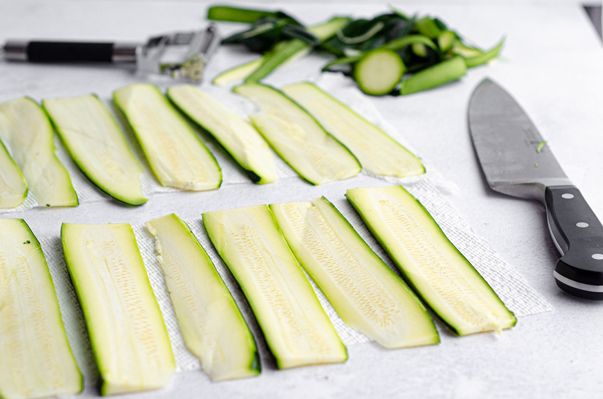 zucchini sliced for zucchini ravioli drying on a paper towel