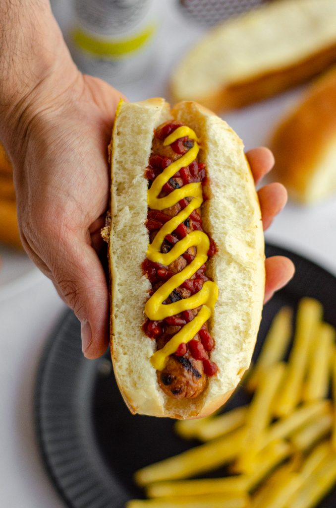 hand holding a hot dog in a homemade hot dog bun with a squirts of ketchup and mustard
