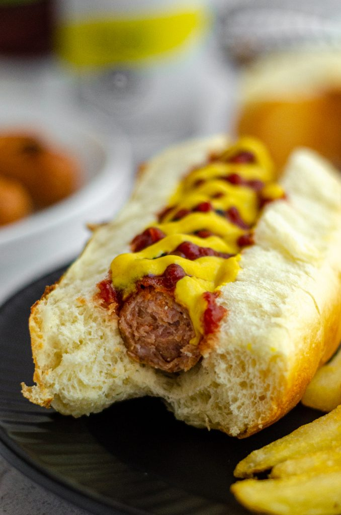 hot dog in a homemade hot dog bun with ketchup and mustard and a bite taken out of it