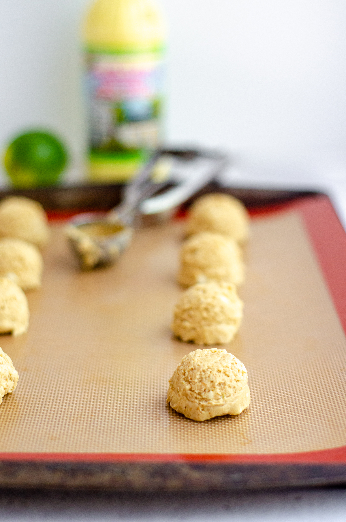 key lime cookie batter dropped into balls on a baking sheet