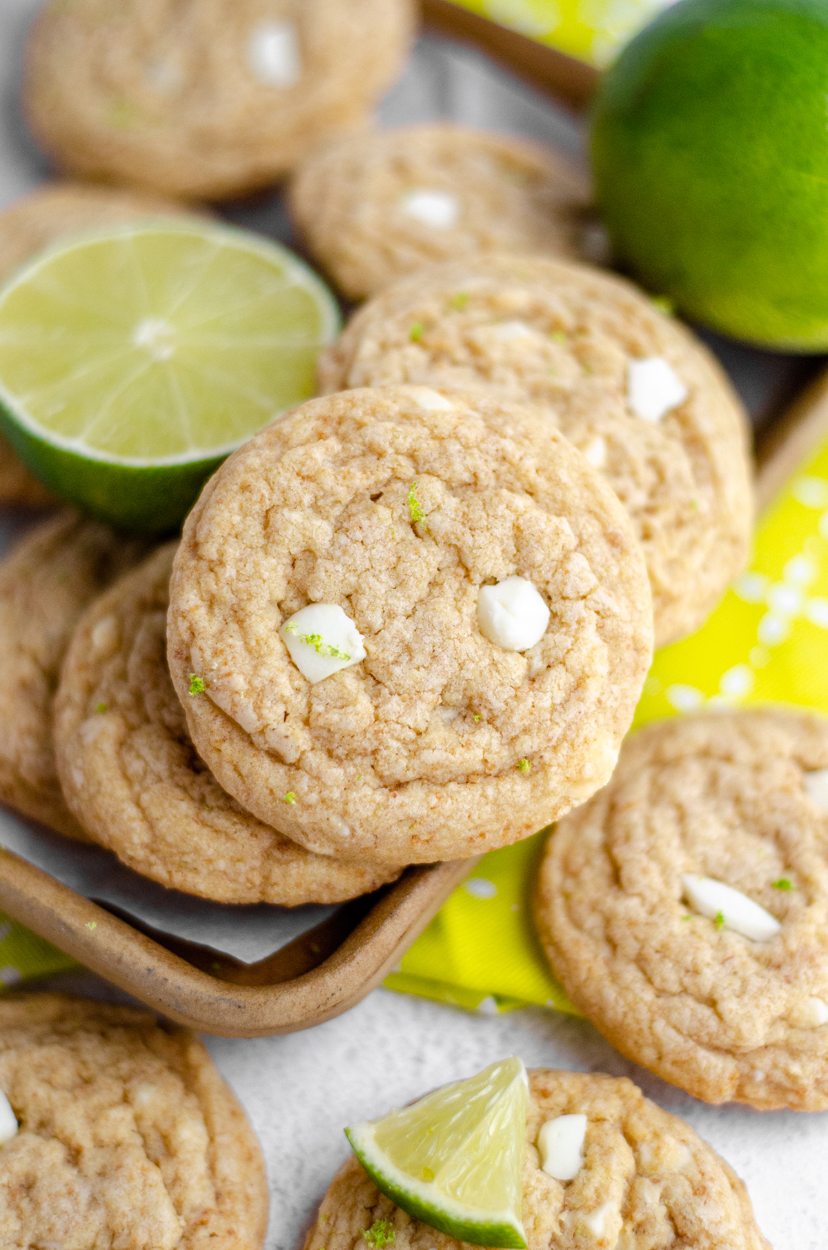 key lime cookies in a pile with fresh limes in the background