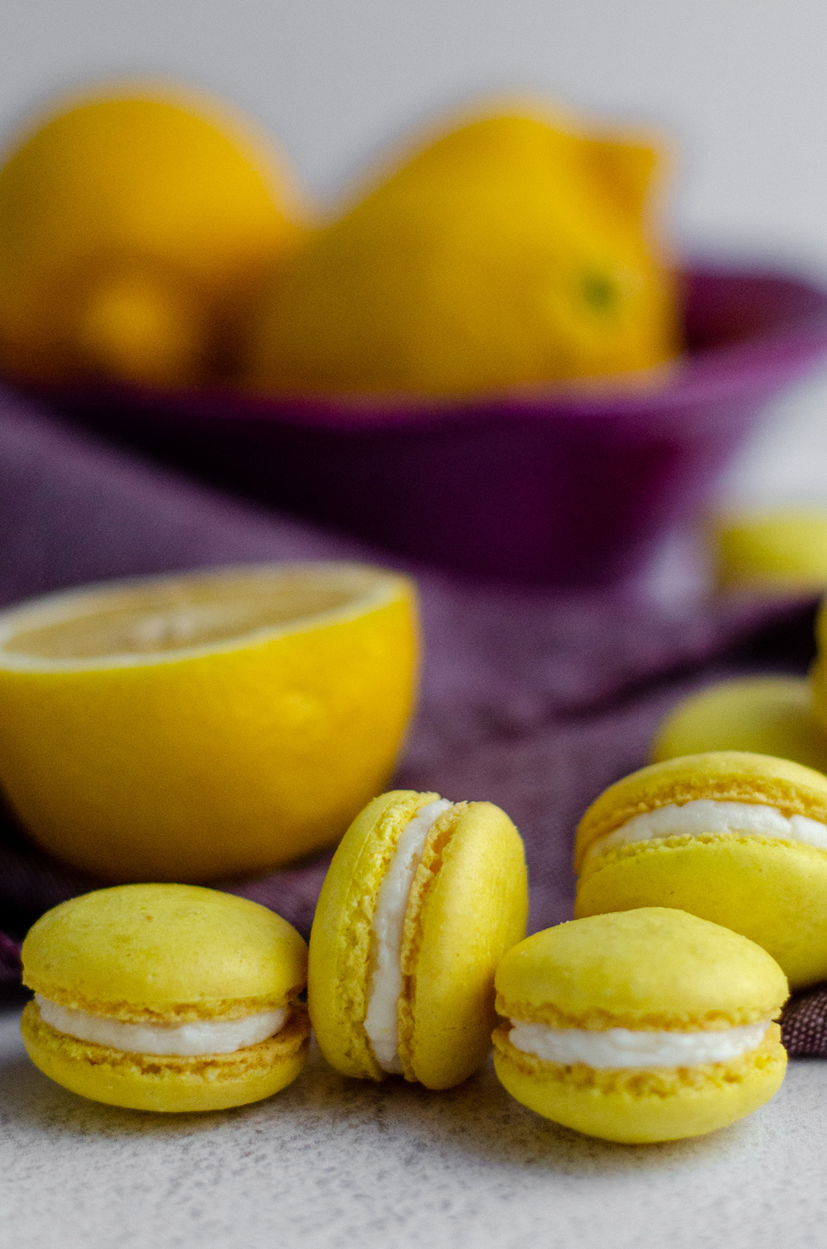 lemon macarons with a purple kitchen towel and sliced lemons in the background