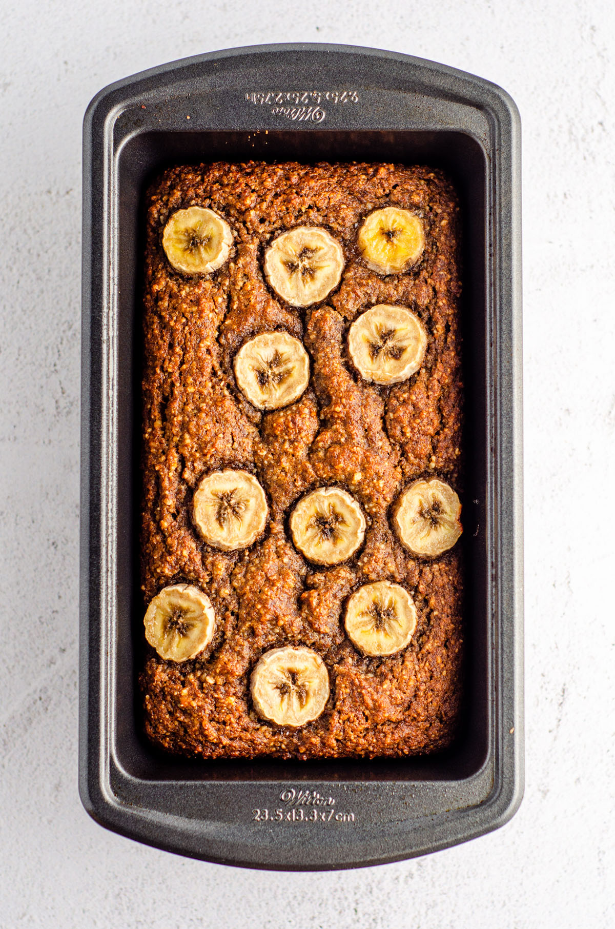 almond flour banana bread baked in a loaf pan with banana slices baked into the top