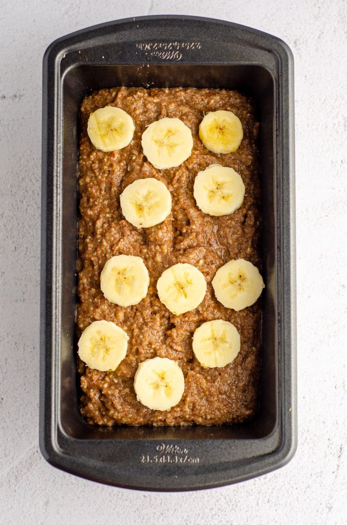 almond flour banana bread batter in a loaf pan with sliced bananas on top of the batter
