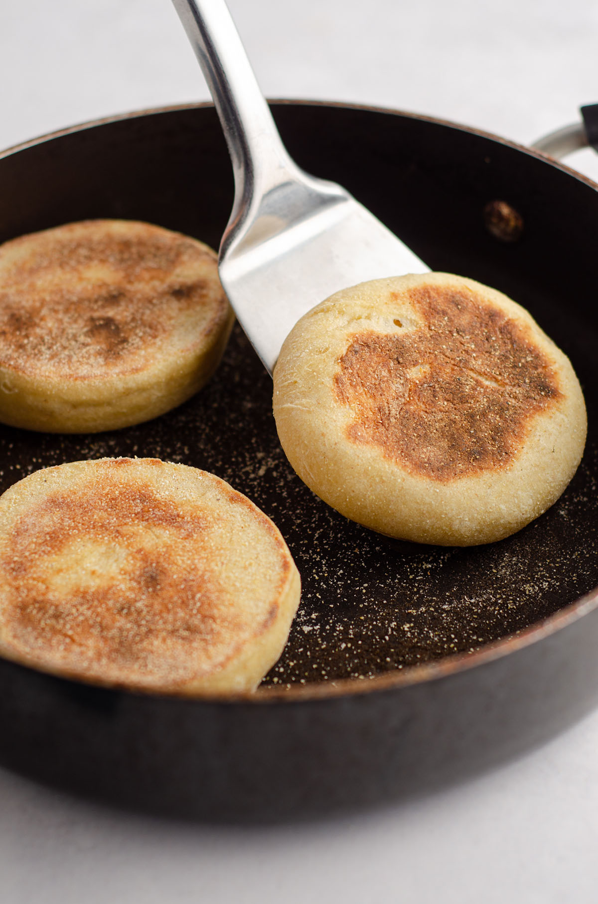 spatula flipping over a sourdough english muffin in a skillet