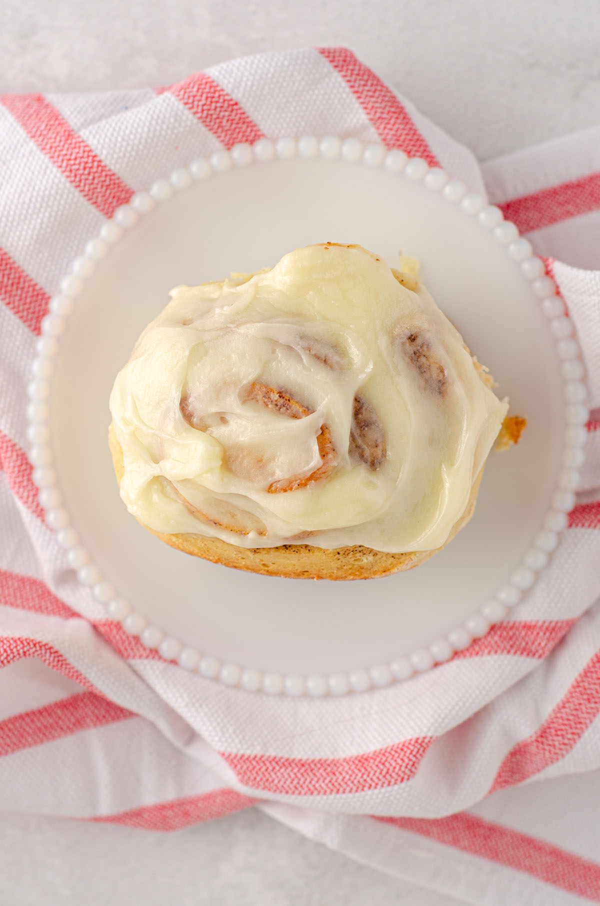aerial photo of sourdough cinnamon roll with cream cheese icing sitting on a white plate with a red and white striped kitchen towel
