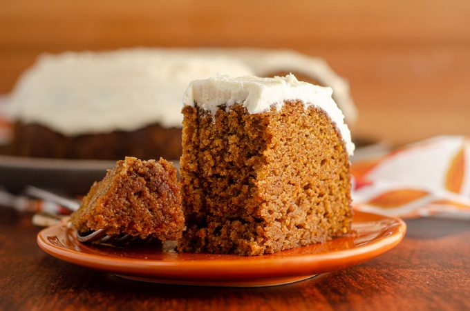 pumpkin bundt cake sitting on an orange pumpkin plate with a bite taken out with a fork
