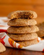 stack of pumpkin spice cookies with a bite taken out of the top cookie