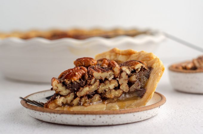 side view of a slice of chocolate chip pecan pie sitting on a plate