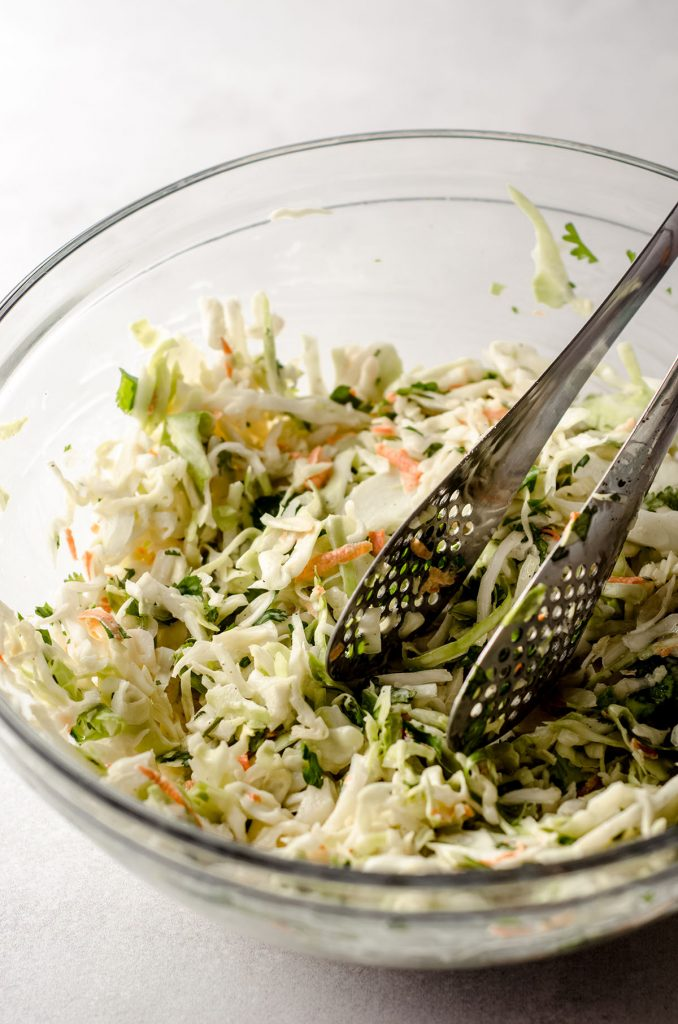 cilantro slaw in a glass bowl with metal tongs for serving