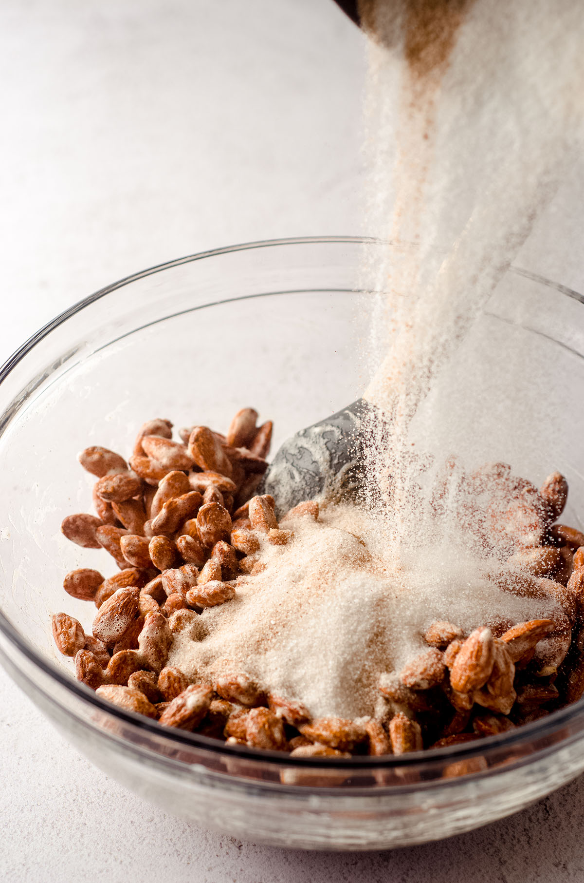 a bowl of almonds coated in vanilla bean paste and frothed egg whites with a bowl of sugar and cinnamon pouring on top to make candied almonds