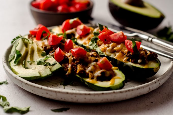 taco zucchini boats on a plate with a fork and a knife