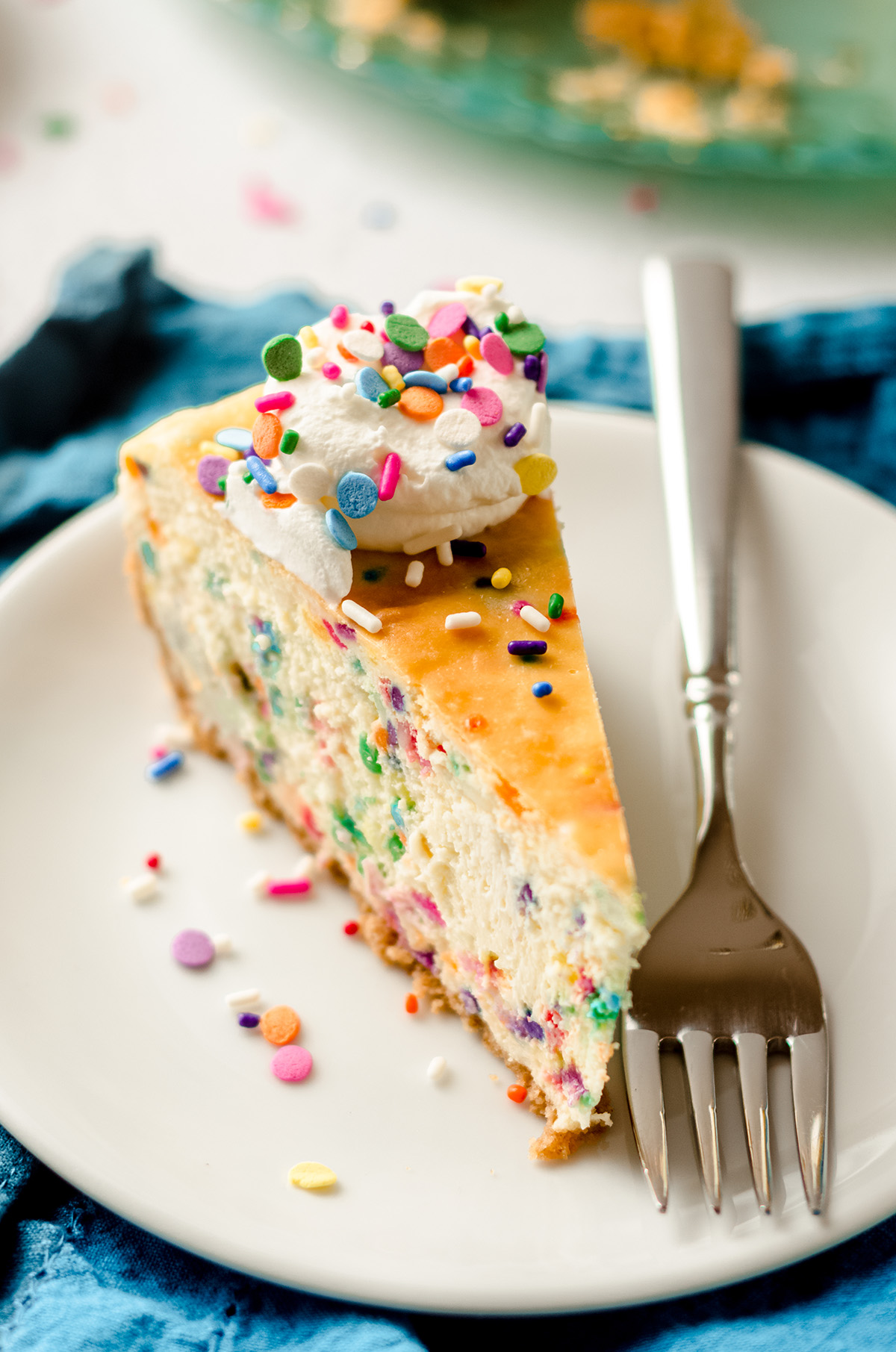 slice of funfetti cheesecake on a plate with a fork