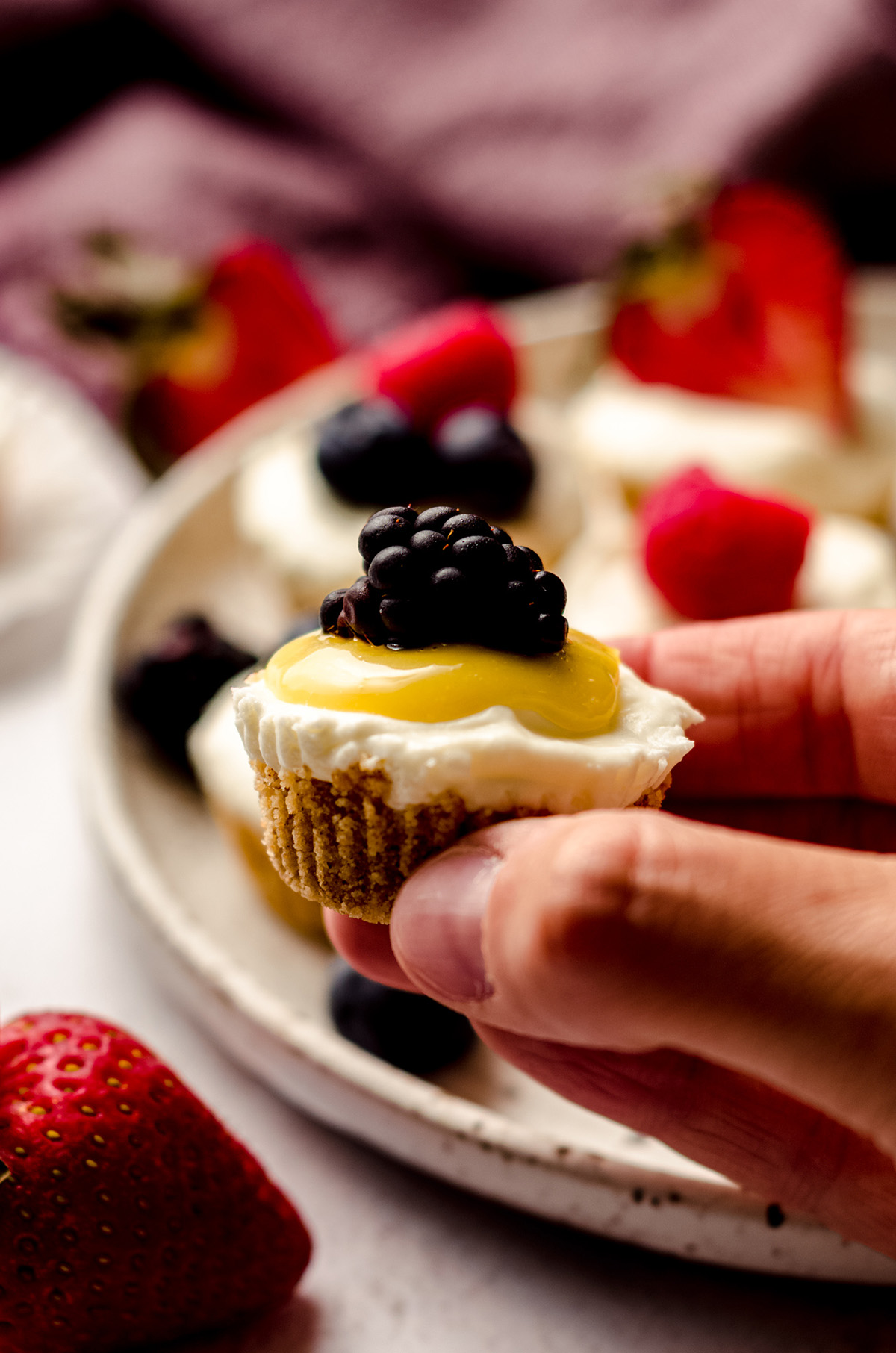 fingers holding a no bake cheesecake bite with lemon curd and a blackberry on top